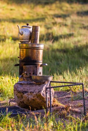 Turkish samovar outdoor. Preparing tea outside on the nature on double pot on the fire.