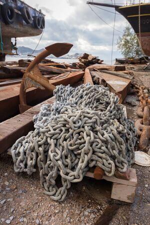 Rusty anchor with chains. Repair boat place outdoor. Bodrum, Turkey.