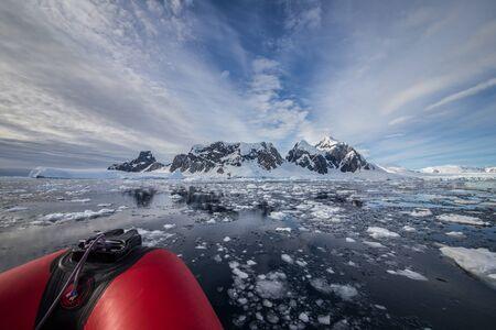 Partie du zodiaque rouge avec paysage d'icebergs en Antarctique. Voyages extrêmes, voile.