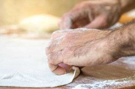 Male hands making dough on table in the kitchen at home