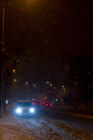 Winter snow storm.Night traffic jam . Car blurred at the street.