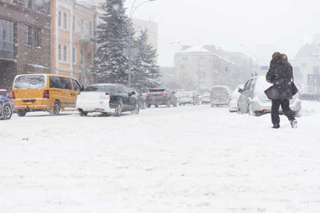 Adult man passing the winter city road in heavy snowy storm. Banco de Imagens