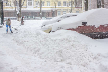Car into snow. Car parked near home parked into snow. Woman cleaning snow. Banco de Imagens