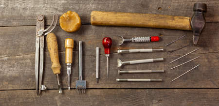 Flat set of leather tool kit for beginners. Old retro instrument for leather working on wood background. Pano. Banco de Imagens