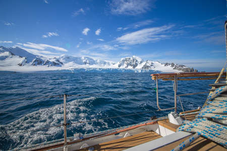 Yacht in Antarctica boating. Icebergs landscape. Extreme travelling, sailing.