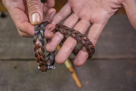 Bracelet leather handicraft. Pigtail accessory. Man s hands making handicraft leather on beautiful old wood background. Polishing tool handmade. Reklamní fotografie