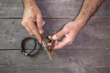 Bracelet leather handicraft. Pigtail accessory. Man s hands making handicraft leather on beautiful old wood background. Reklamní fotografie
