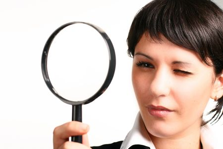 The  girl searches for something through a magnifier photo