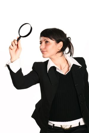 The  girl searches for something through a magnifier up photo