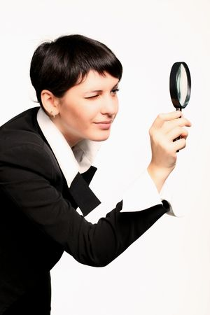 The business girl searches for something through a magnifier