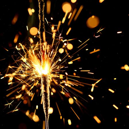 sparkler firework flame on black photo