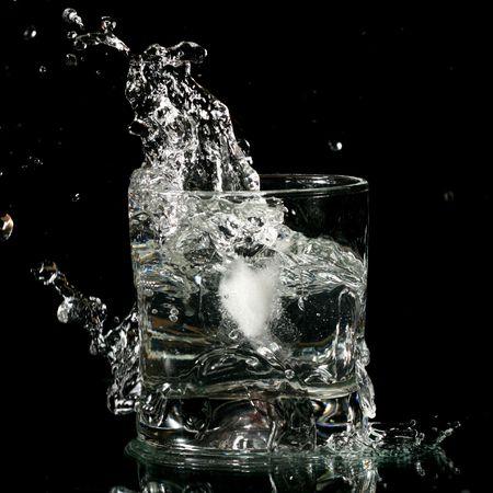 alcohol splash on black background close up photo