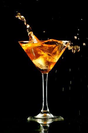 bartend: alcohol splash in martini glass on black background Stock Photo