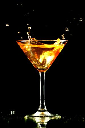 alcohol splash in martini glass on black background Stock Photo