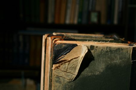 untidiness: books on table in dark library room
