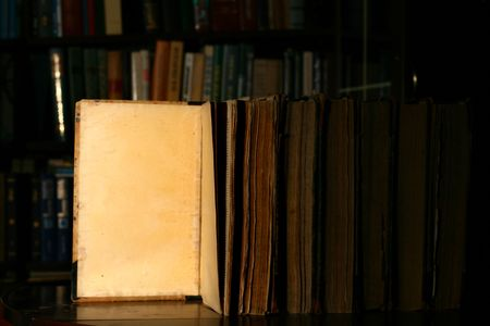 books on table in dark library room photo