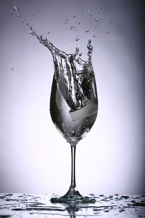 alcohol splash on gray background Stock Photo