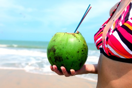 girl holding coconut cocktail in hands photo