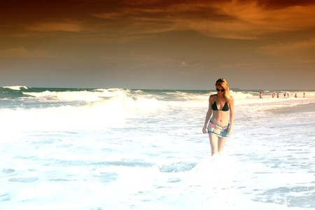 girl walking in the ocean waves photo