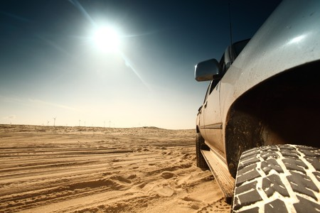 yellow adventure: truck in desert sand and blue sky