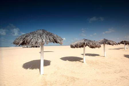 umbrella in desert under blue sky photo
