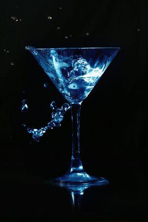 bartending: martini splash on black background close up