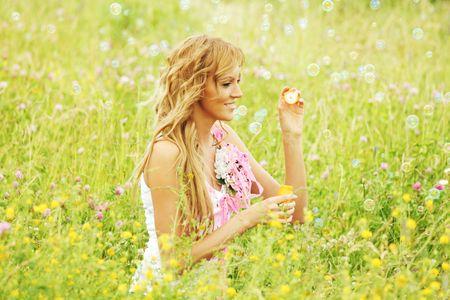 Blonde starts soap bubbles in a green field Stock Photo - 6314712
