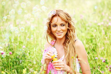 Blonde starts soap bubbles in a green field Stock Photo - 6317738