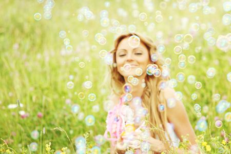 Blonde starts soap bubbles in a green field Stock Photo - 6317362