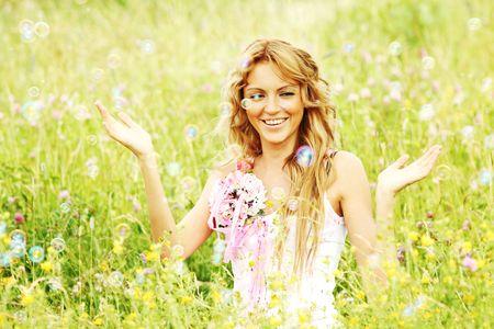 Blonde starts soap bubbles in a green field Stock Photo - 6317809