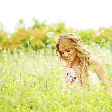 Blonde starts soap bubbles in a green field Stock Photo - 6316777