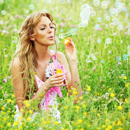 Blonde starts soap bubbles in a green field photo