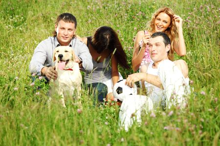 friends and dog in green grass field Stock Photo - 6318188
