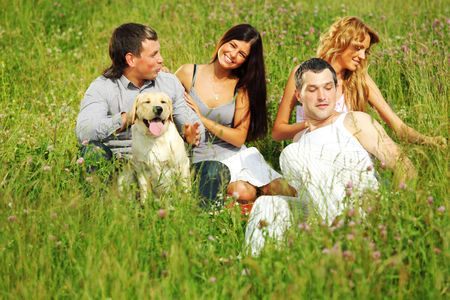 friends and dog in green grass field Stock Photo - 6318153