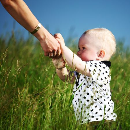 boy and mother hands in grass field Stock Photo - 6360622
