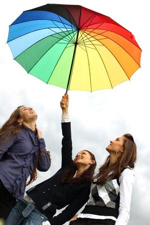 girlfriends stay under colourful umbrella  photo