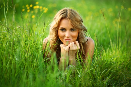 blonde lays on green grass Stock Photo - 8415521