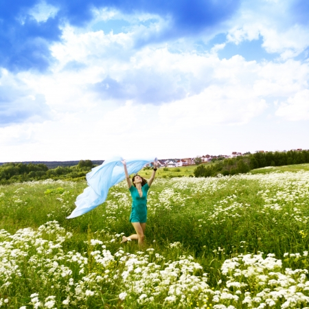 girl run by field fabric in hands fly behind like wings