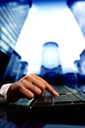 reseller work on keyboard skyscrapers on background photo