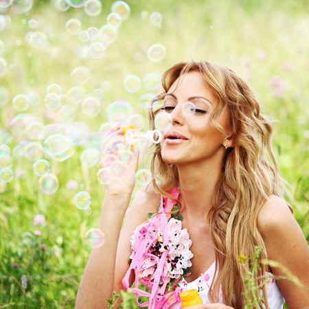 Blonde starts soap bubbles in a green field Stock Photo - 8439496