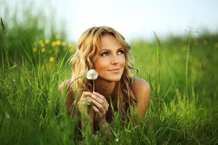 natural face: girl blow on dandelion on green field Stock Photo