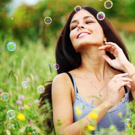 donna felice sorriso, bolle di sapone di erba verde intorno