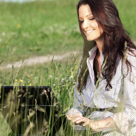 girl with laptop on green grass photo