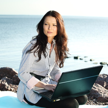 student travel: woman with laptop sea background