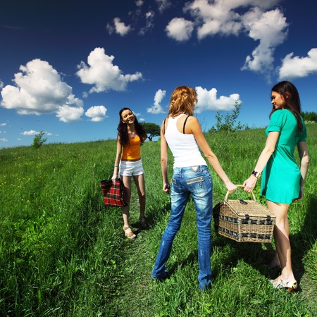 girlfriends on picnic in green grass field photo