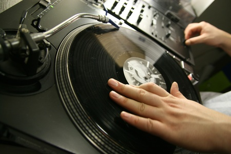 scratch battle of dj playing on his vinyls hand on photo