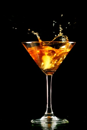 alcohol splash in martini glass on black background photo