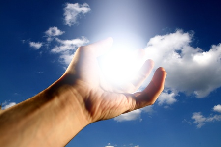 raising hands: light in hand god bless to you Stock Photo