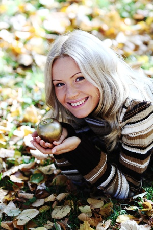 woman with golden apple in autumn park Stock Photo - 8587704