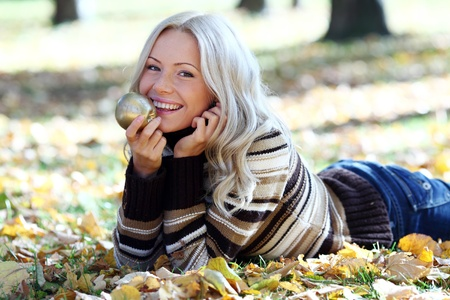 woman with golden apple in autumn park Stock Photo - 8586218